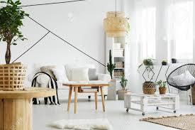hölzerne und weiße möbel in gemütlichem wohnzimmer im scandi stil