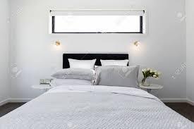 luxuriöses modernes schlafzimmer mit goldenen wandleuchten und grauer decke