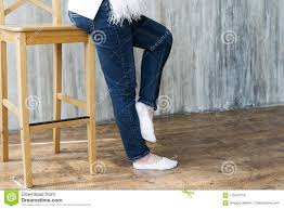 Legs In Jeans On The High Chair Of The Pregnant Girl. Stock ...