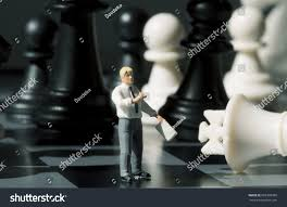 Businessman And Chess Figures On Game Board Playing With Miniature Doll Macro Photo