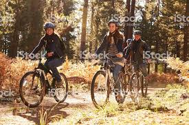 Group Of Smiling Friends Riding Bikes In A Forest Royalty Free Stock Photo