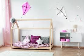 kissen auf bett und weißem schrank mit rosa zubehör gegen weiße wand mit diy drachen im schlafzimmer des gemütlichen mädchens
