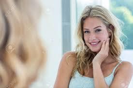lächelnde schöne junge frau die sich zu hause im badezimmerspiegel betrachtet