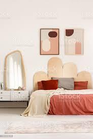 echtes foto einem kingsizebett mit kissen und decke stand neben einem regal mit spiegel im schlafzimmer interieur mit plakaten an eine wand und