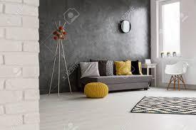 große gemütliche grauen wohnzimmer mit holz hellen boden durch die wand sofa mit bunten kissen
