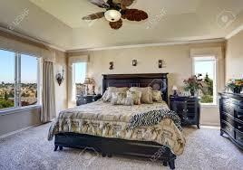 luxus interieur des master schlafzimmer mit schwarzen möbeln king size bett mit kopfteil und tropischen gemusterten bettwäsche northwest usa