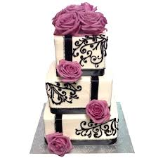 White frosted cake with black piping ribbon and purple roses