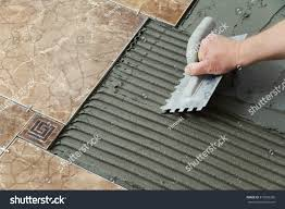 laying ceramic tiles troweling adhesive onto stock photo 310563206