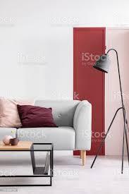 vertikale ansicht pastell rosa und bordeaux kissen grau sofa im eleganten skandinavischen wohnzimmer mit roten rosa und weißen wand mit