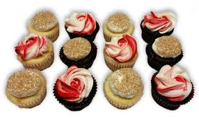 12 Cupcakes Decorated To Look Like Roses And Also Topped With Gold Sprinkles