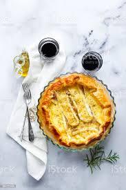 traditionelle französische quiche lorraine mit camembert oder brie käse mit birnen und rosmarin auf einem weißen marmor tisch hausgemachte kuchen aus
