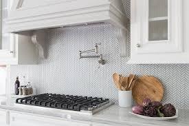 white and gray herringbone backsplash tiles by sacks