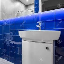 elegantes badezimmer mit blauen glänzenden fliesen spiegel und waschbecken
