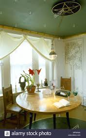 Modern Dining Room With Green Painted Ceiling White Curtains Over A Sunny Window And Round Wood Table Chairs