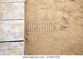 Top View Brown Sand With Footprint On The Ground Floor And Grid Cement Pathway