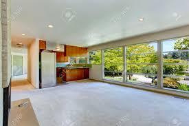 leeres haus interior wohnzimmer mit glaswand und teppichboden blick auf kleine küche