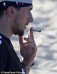 johnny manziel puffs on suspicious looking cigarette while
