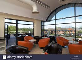 Seating Coffee Area In Modern Office Building For Staff With Orange And Black Chairs View Through Window