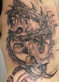 Black Ink Dragon Wrap Around Skulls Tattoo On Left Side Rib