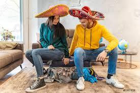 foto auf lager ein junges paar im sombrero bereitet die koffer für die nächste reise im wohnzimmer vor