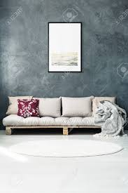 helles plakat auf dunkler wand über beige sofa mit kissen im wohnzimmer mit rundem teppich
