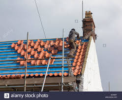 a tiler replacing roof tiles on a house stock photo royalty