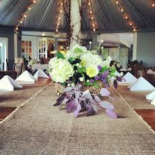 A Country Wedding Reception Table Looks Gorgeous With Flowers And Burlap Runner