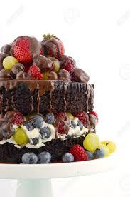 köstlich göttlichen schokolade kuchen mit erdbeeren heidelbeeren himbeeren und trauben und sahne auf hellblauen shabby chic tisch
