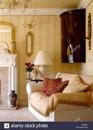 antike eckschrank und cremefarbenen sofa mit fransen in