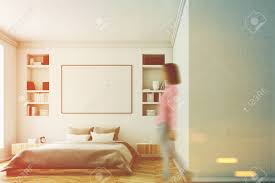 frau in einem modernen luxus schlafzimmer mit weißen wänden ein großes bett in der mitte des raumes zwei bücherregale ein großes fenster und ein