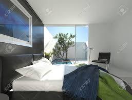 gehobenen schlafzimmer mit einem schwarzen leder doppelbett auf einer kreisförmigen podest und boden bis zur decke glastüren die zu einem sonnigen