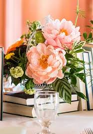 Coral Charm Peony Centerpiece Atop A Pile Of Book Krisztina Wesley VIEW PHOTOS Rustic Roots Design Logo