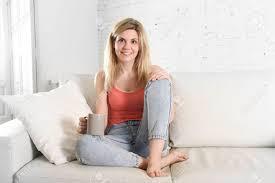 junge attraktive haare frau mit tasse kaffee auf dem sofa zu hause wohnzimmer lächelnd glücklich und entspannt lifestyle konzept sitzen
