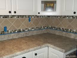 simple kitchen area with brown ceramic glass border tile
