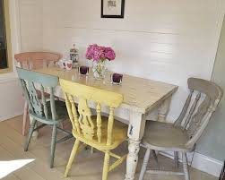 shabby chic farmhouse dining table with four multicoloured chairs