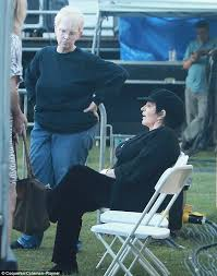 liza minnelli helped to her chair as reclusive star is pictured