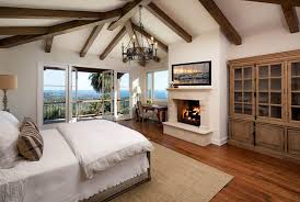 Mediterranean Style Master Bedroom With Red Oak Flooring Chandelier And Balcony Views