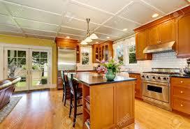 entwurf der braunen holz küche mit stahlgeräten bar küche insel mit frischen blumen und pendelleuchten northwest usa