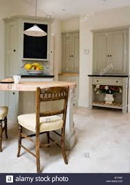 Antique Chairs At Breakfast Bar In Modern Kitchen With Limestone Flooring And Pale Gray Fitted Units