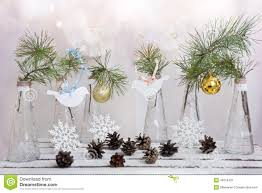 christmas decorations on a branch of tree in glass vases stock