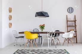 schöne weiße esszimmer mit einem großen tisch und designerstühle