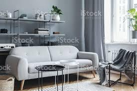 moderne und helle nordische wohnzimmer mit designsofa mit kissen couchtisch pflanzen stilvolle accessoires und buchständer an der grauen wand braune
