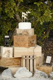 A Single Tier Perfectly White Ruffled Cake Topped With Miniature Handmade Flags Sits Like An Ornate Crown On Tower Of Rustic Wine Crates