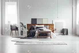 holzbank und grauer stuhl nahe kingsize bett gegen weiße wand mit kopienraum im schlafzimmer mit fenster und gemälden