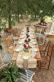 Rustic Country Wedding Reception Decorations With Colorful Flowers On Long Wooden Table Also Small Chairs Around Lush Vegetation