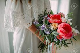 Bride Holds In Hands A Rustic Wedding Bouquet With White Roses And Crimson Peonies On Window