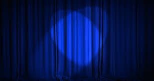 a blue velvet curtain opening with spotlights in a theater