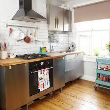 Small Kitchen With Wood Flooring Stainless Steel Cabinetry White Tiled Splashback And Blue