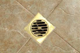 sewer grate drain water on the tile floor in bathroom stock photo