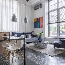 helles wohnzimmer mit sofa sessel und großem fenster mit jalousien
